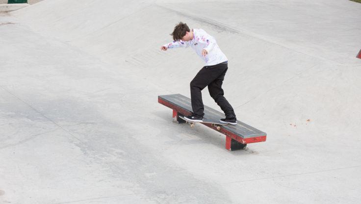 Glide med et skateboard på en benk i skateparken