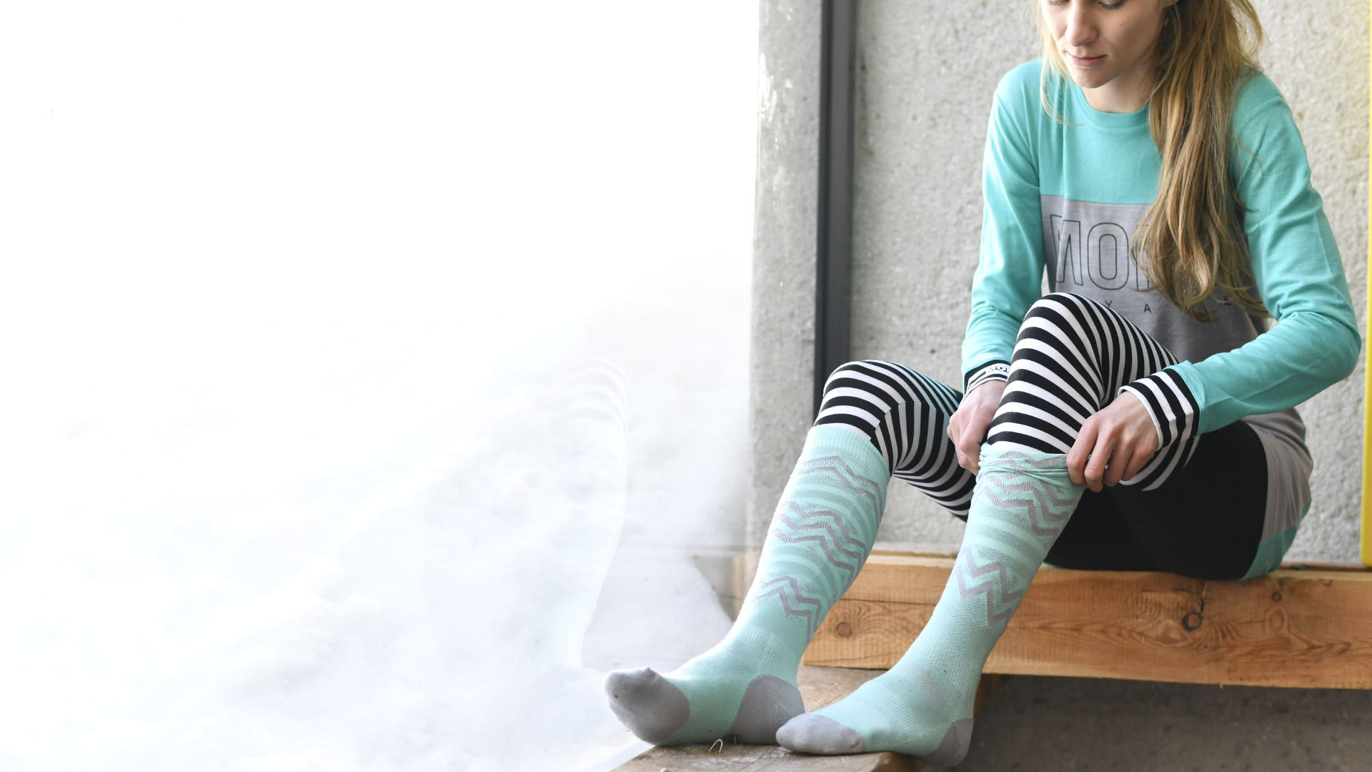A girl in a base layer putting on a pair of ski or snowboard socks by Mons Royale