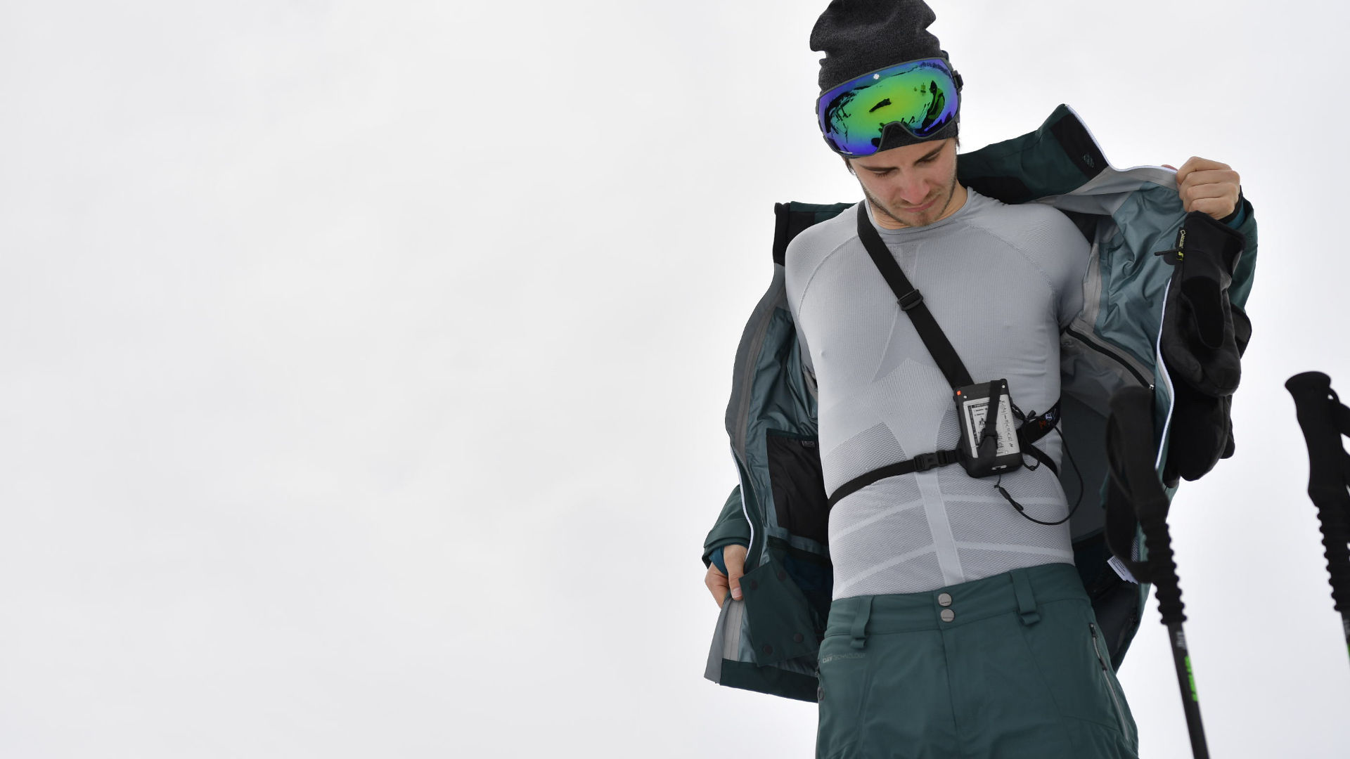A skier taking off his jacket to show his synthetic base layer and transceiver