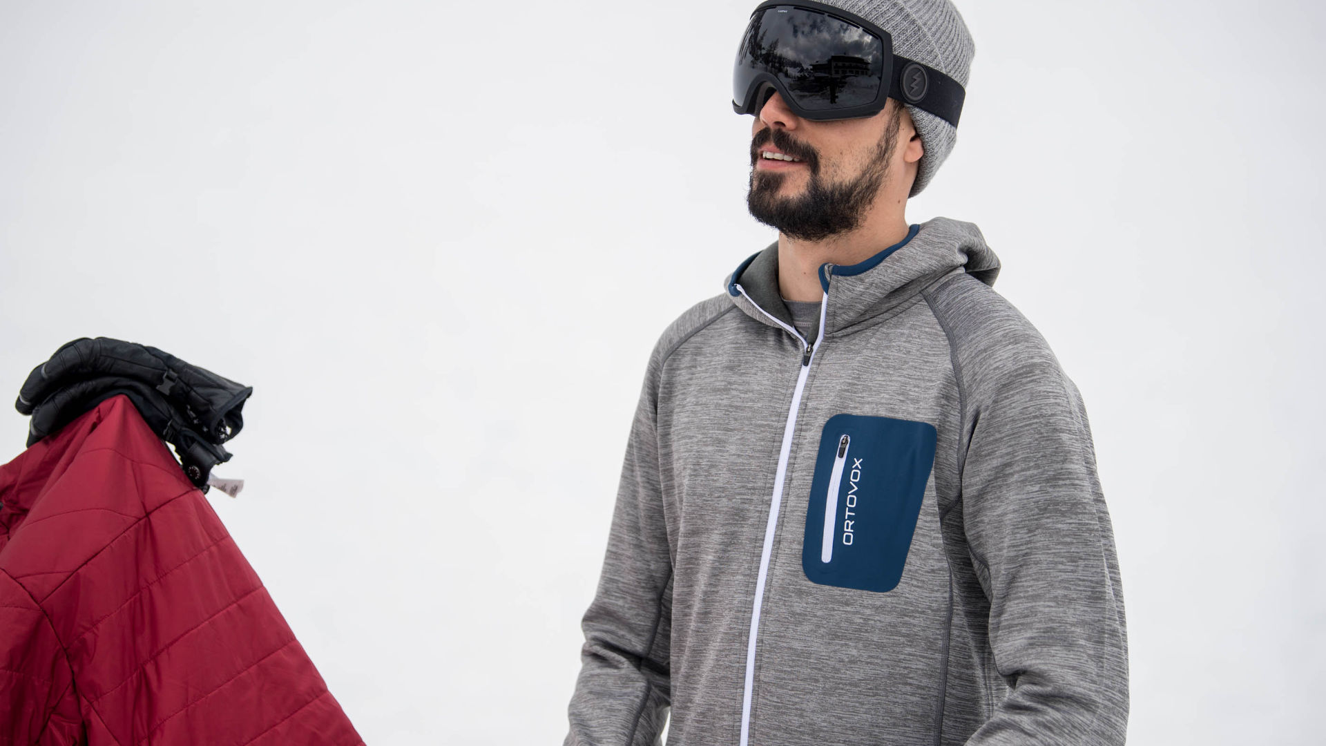 Snowboarder taking a break from riding in his fleece mid-layer from Ortovox