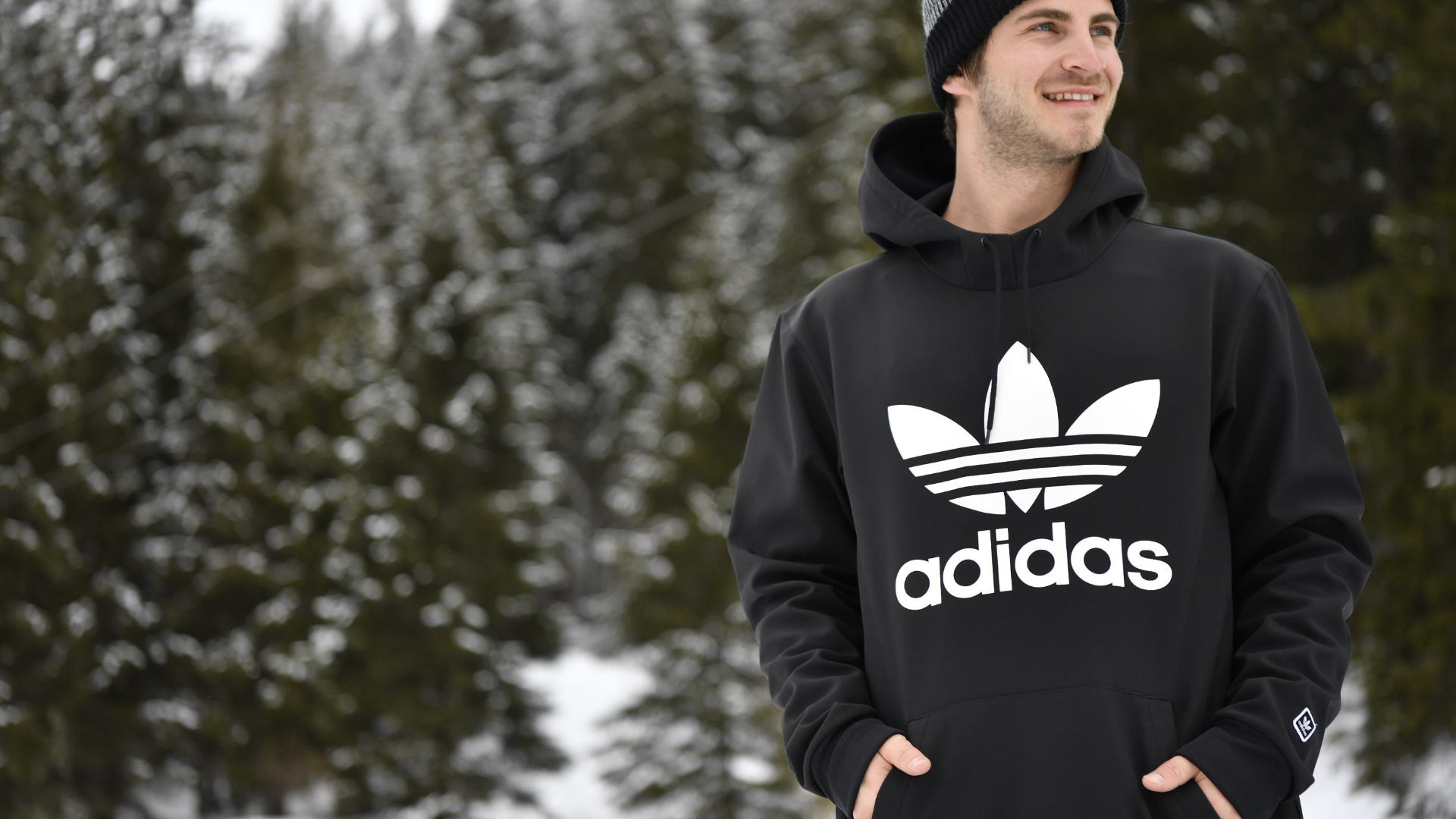 A male snowboarder outside wearing a black shred hoodie from adidas