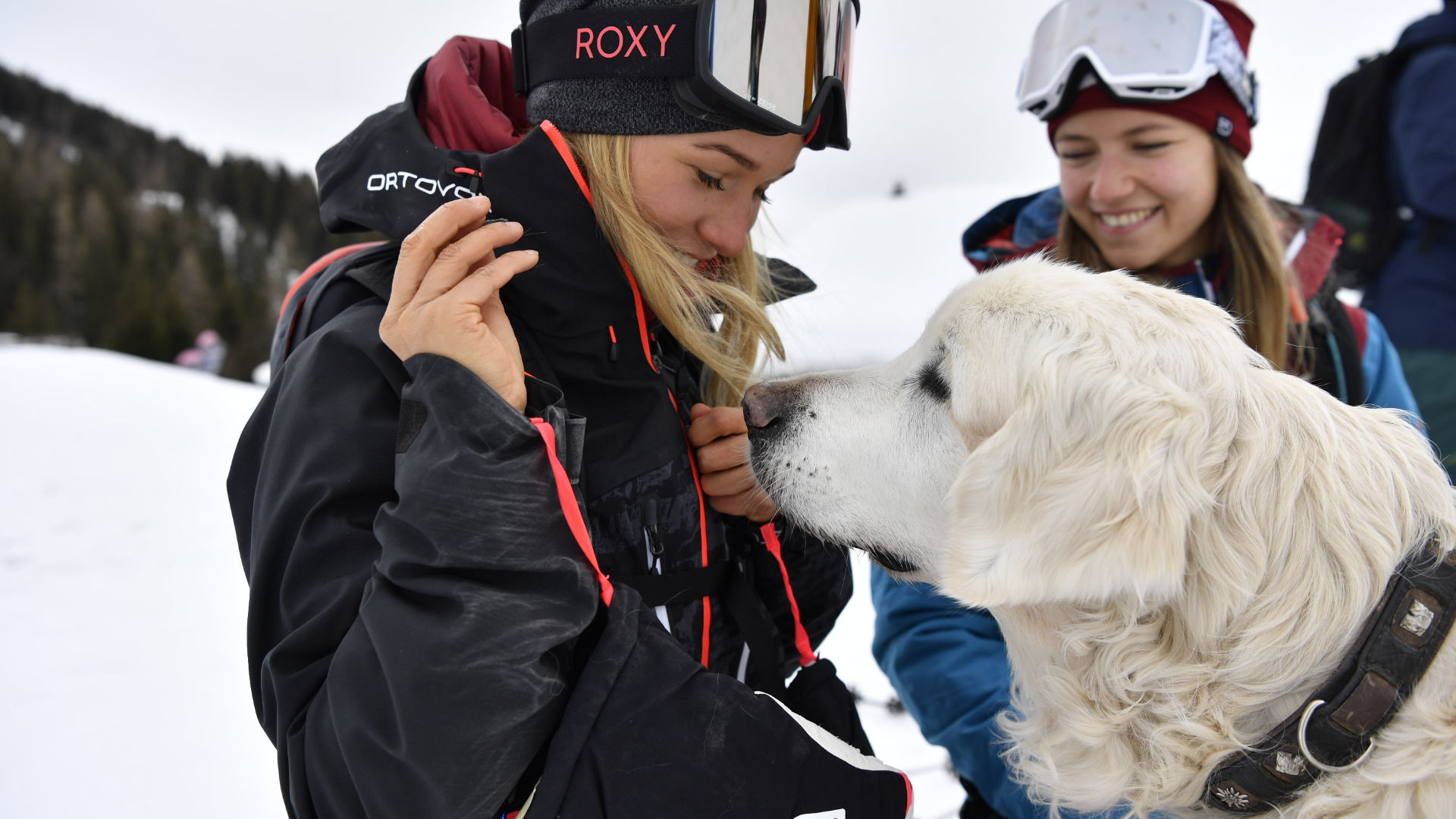 A female rider in a snowboard jacket playing with a dog