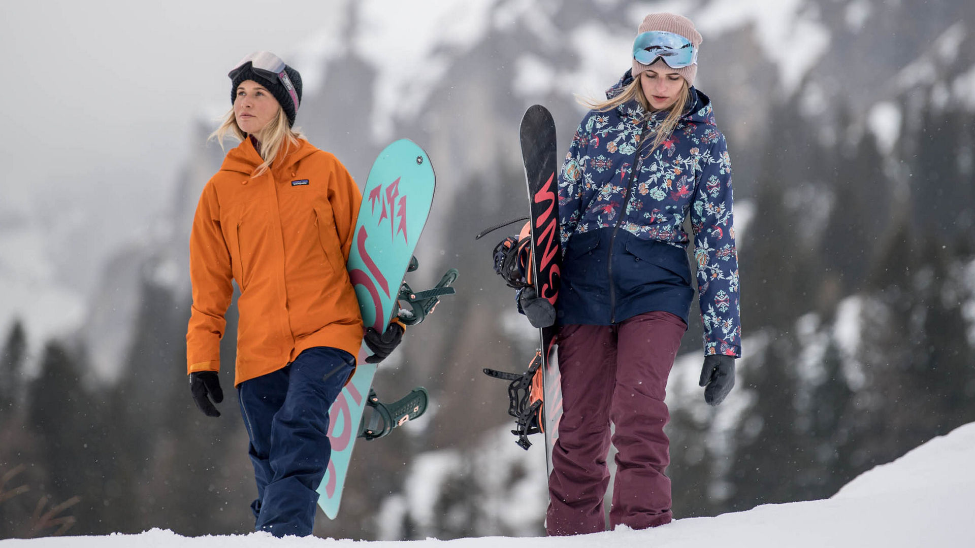 Two women walking with their snowboard in the mountains equipped with snowear from Patagonia