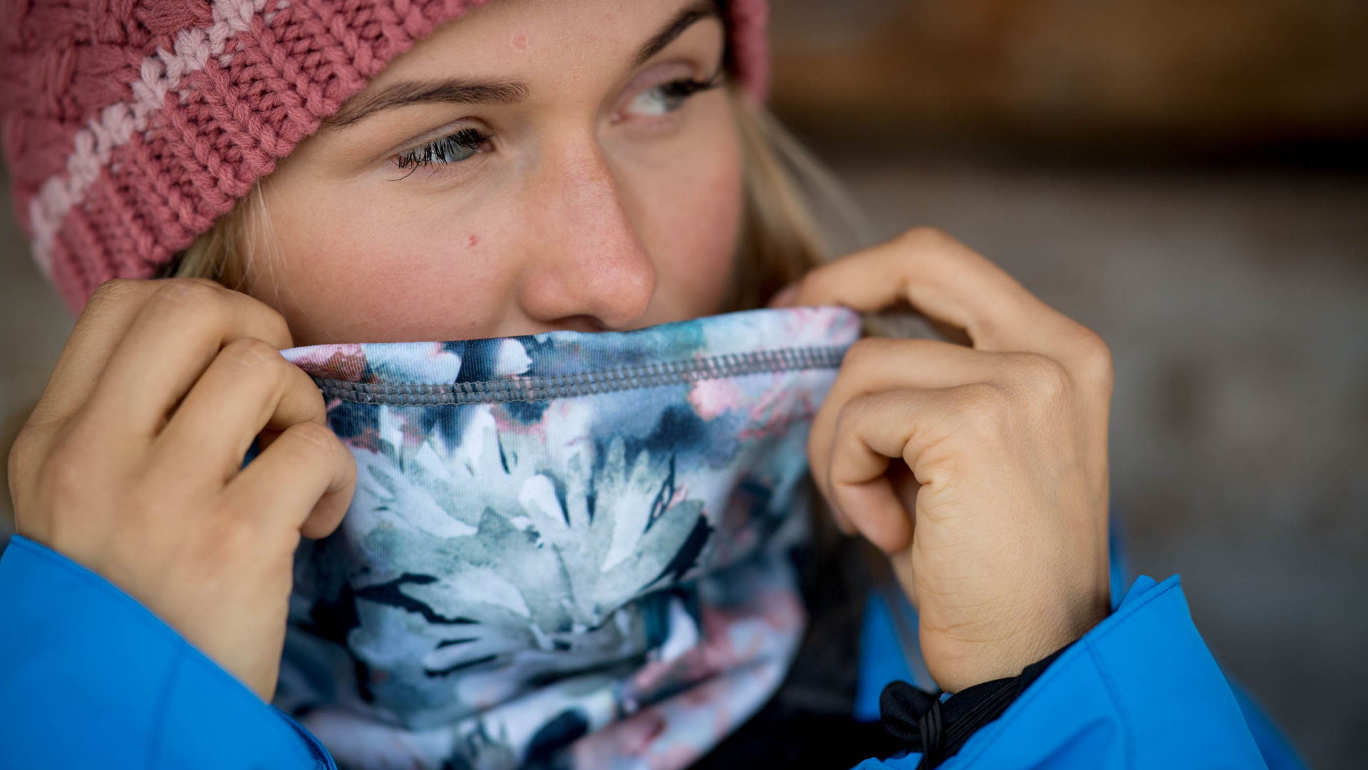 Female snowboarder outside pulling her bandana over her mouth