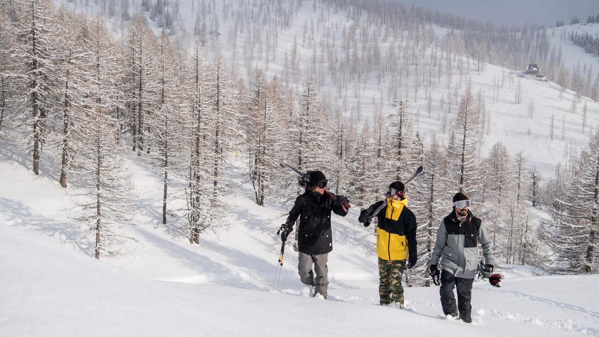 Three freeskiers walking in snow in Hochkeil