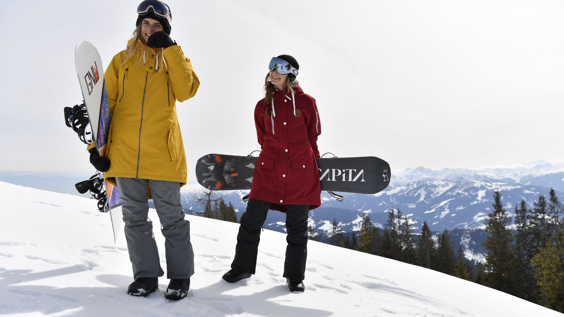 Two snowboarders chilling with longer cut jackets