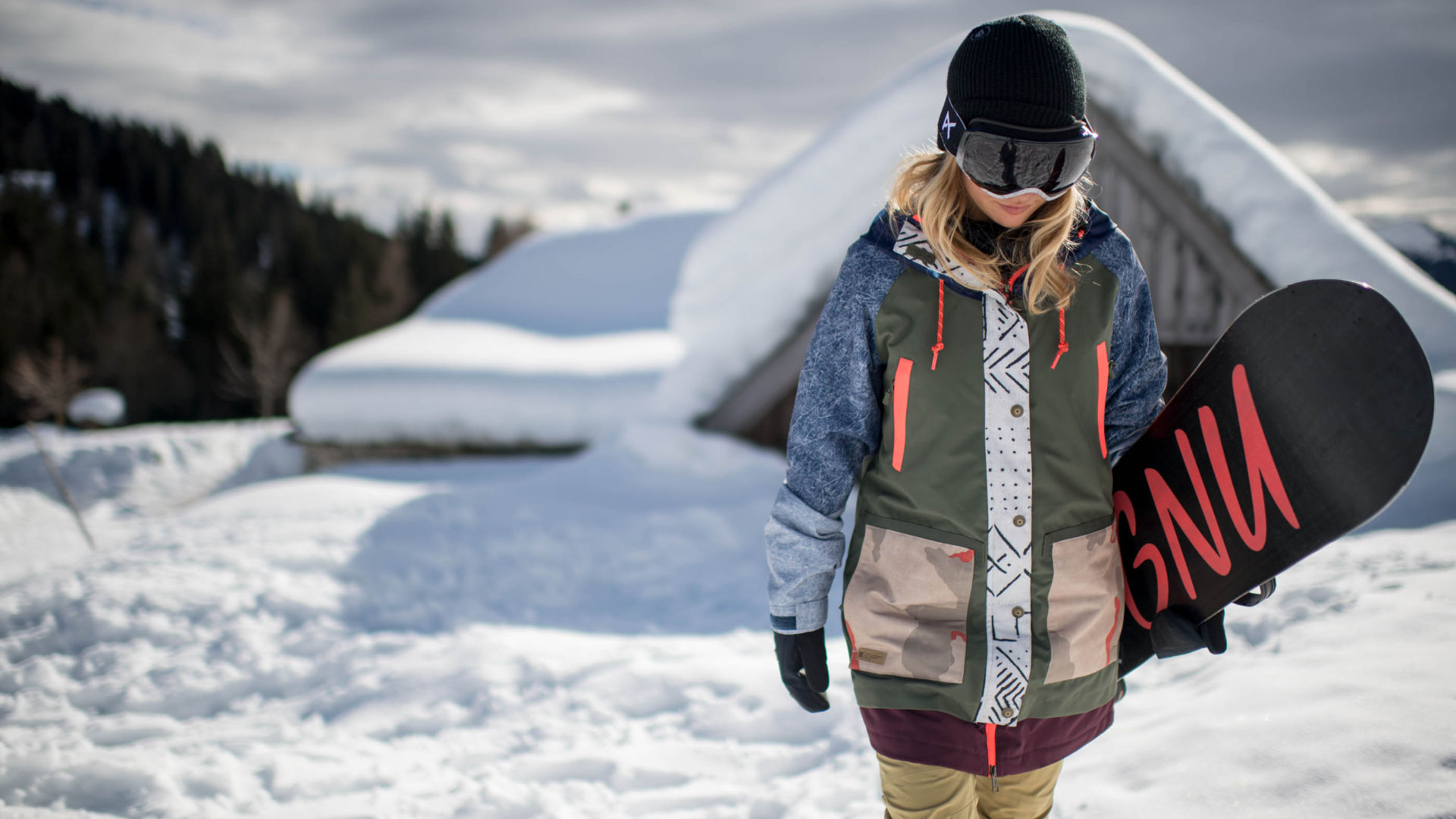 Female snowboarder in front of a hut wearing loose fit outerwear
