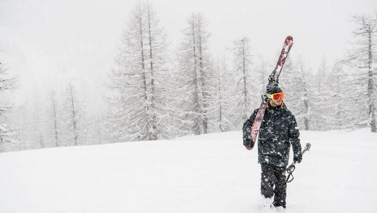 Eine Skifahrer der bei starkem Schneefall mit seiner stark isolierten Jacke unterwegs ist