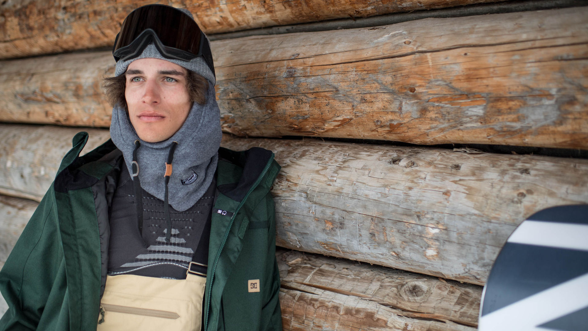 Male snowboarder staning outside in front of a hut with a medium insulation jacket