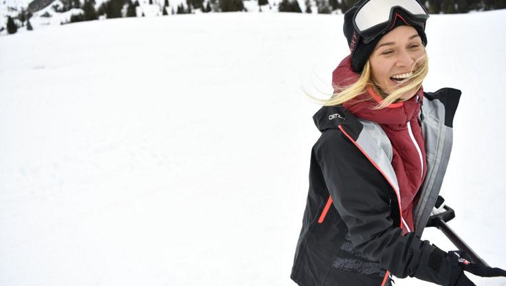 Eine Snowboarderin die in ihrer Shell-Jacke Schnee schaufelt