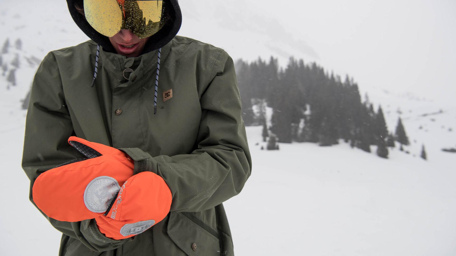 a snowboarder adjusting his bright orange mittens