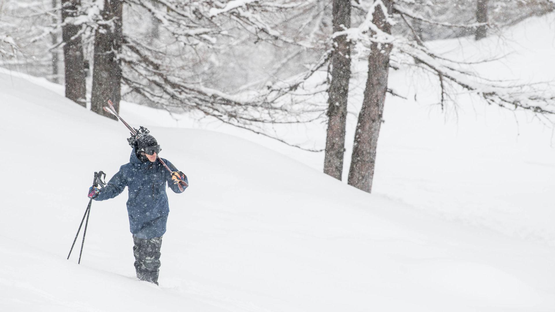 Freeskier hiking in heavy snowfall