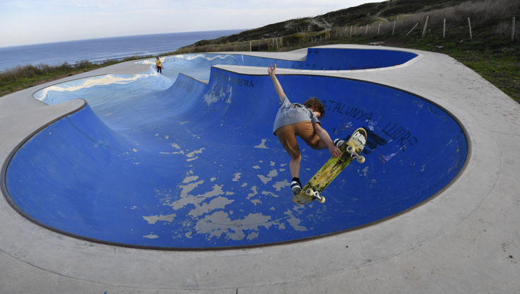 Boy skateboarding in a bowl. He is doing a stalefish air.
