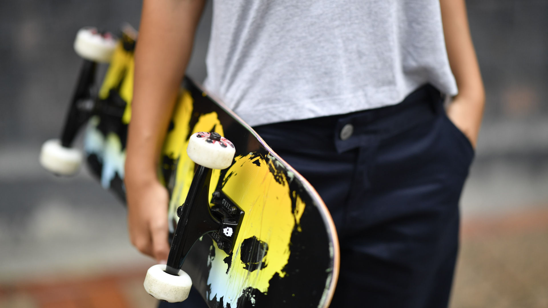 Holding a Bloody Rainbow skateboard by Zero with the wheelbase showing