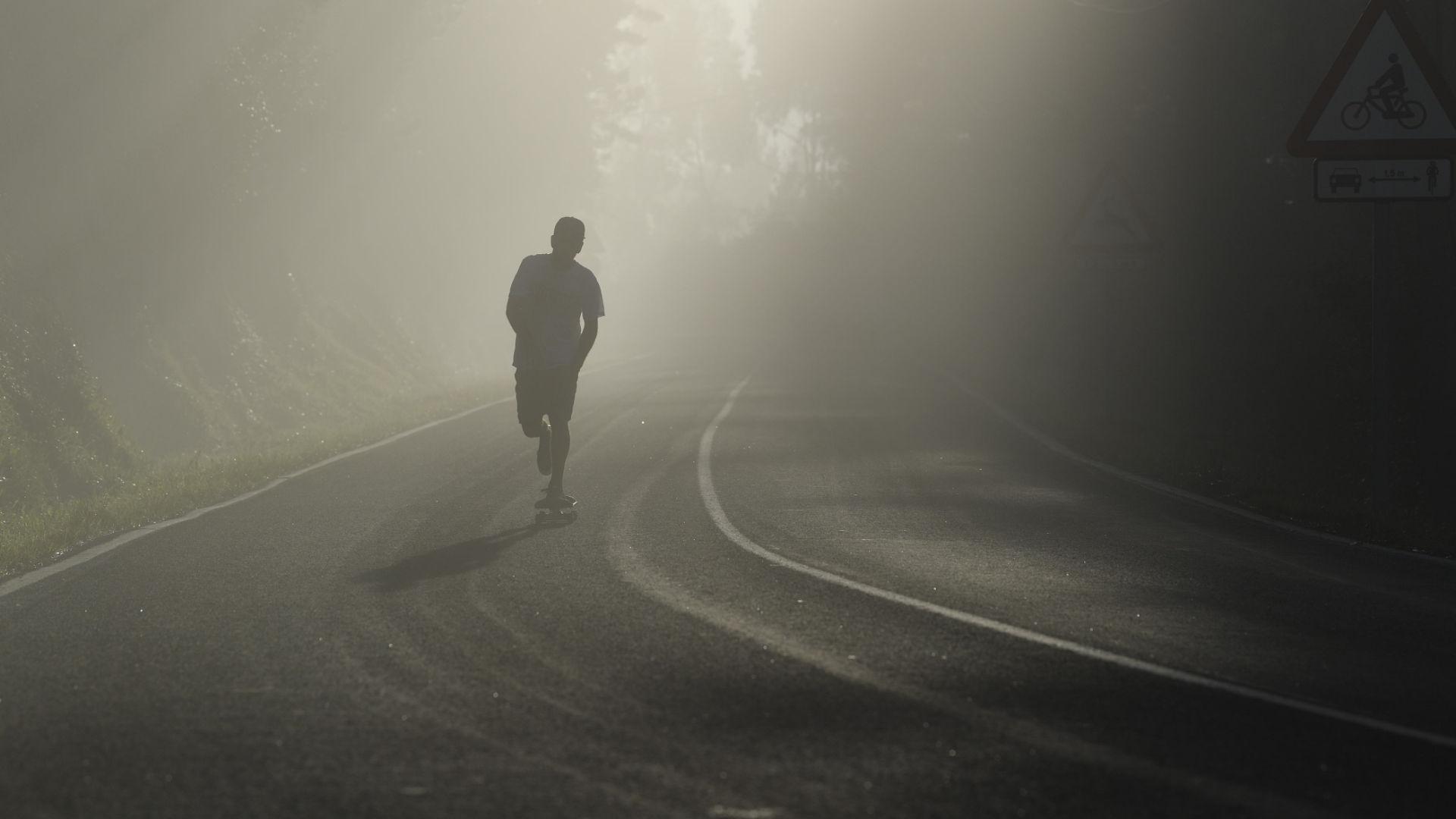 Ein Junge rollt auf seinem Skateboard mit großen Rollen dem Sonnenaufgang in Spanien entgegen