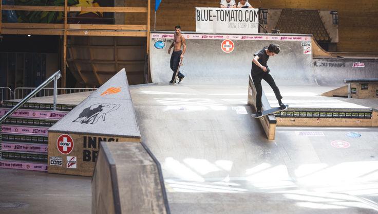 Skateboarder sliding on his board with medium wheels at the skatepark