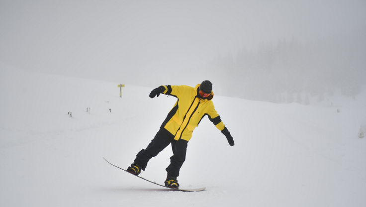 Snowboarder jumping in the powder between the trees with his medium-flex Lib Tech snowboard