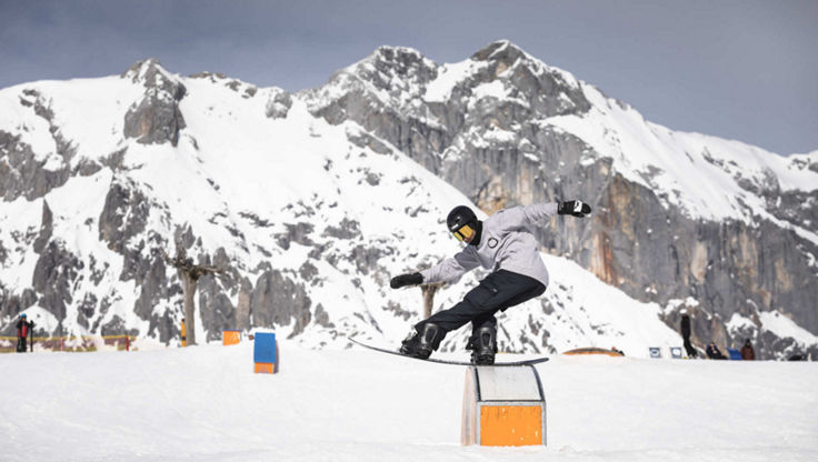 Freestyle snowboarder doing a trick on a box in the snowpark, with a soft board