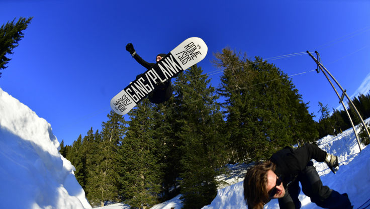 Two snowboarders doing tricks on a rail with quite short boards