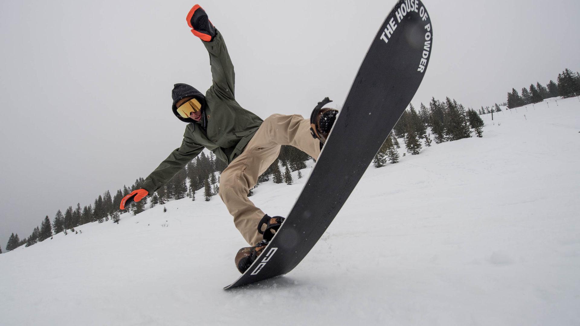 Snowboarder flext sein Board am Hochkeil