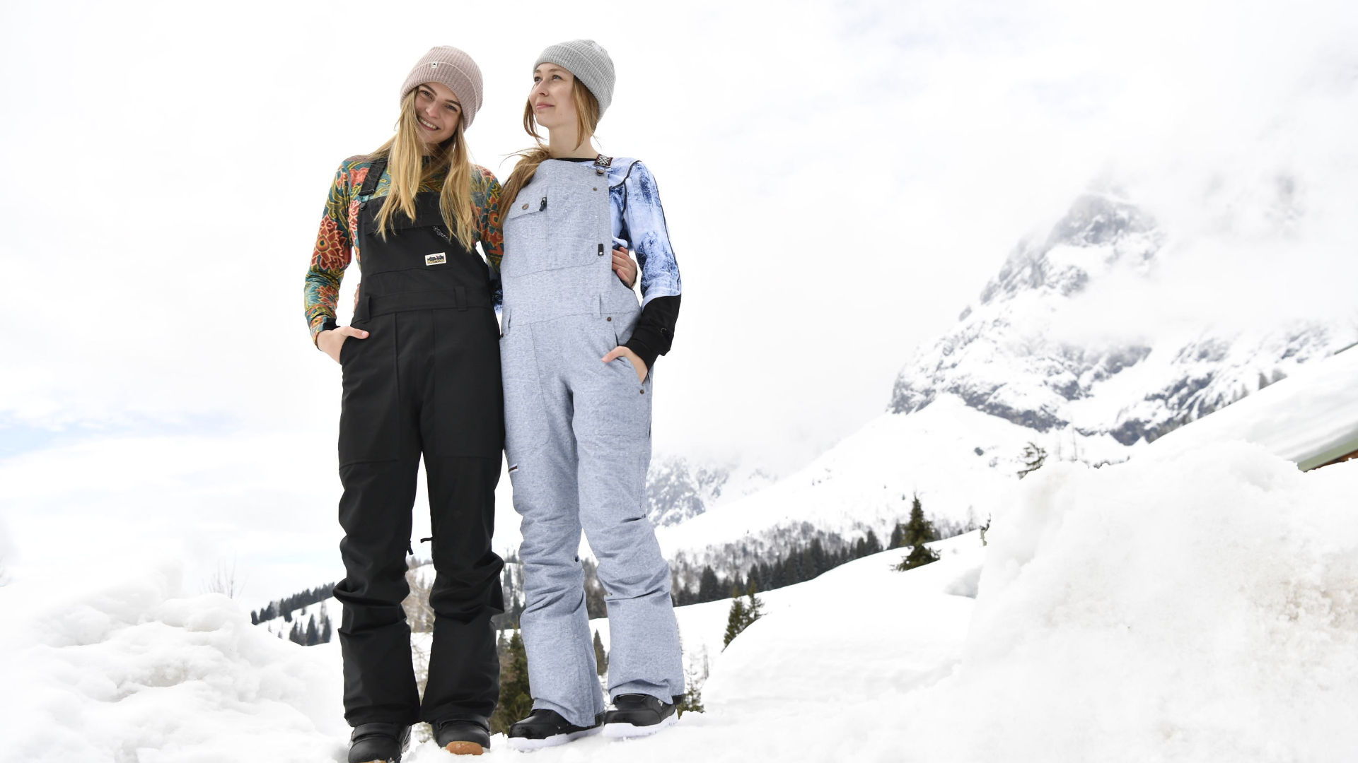 Two female snowboarders standing in snow on the moutain in snowboardpants