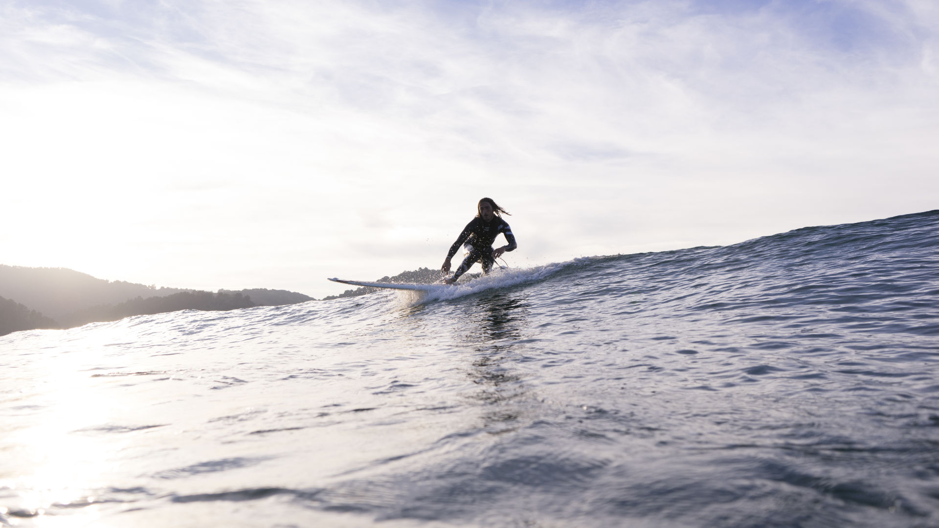 Surfer riding in cold water in a full wetsuit