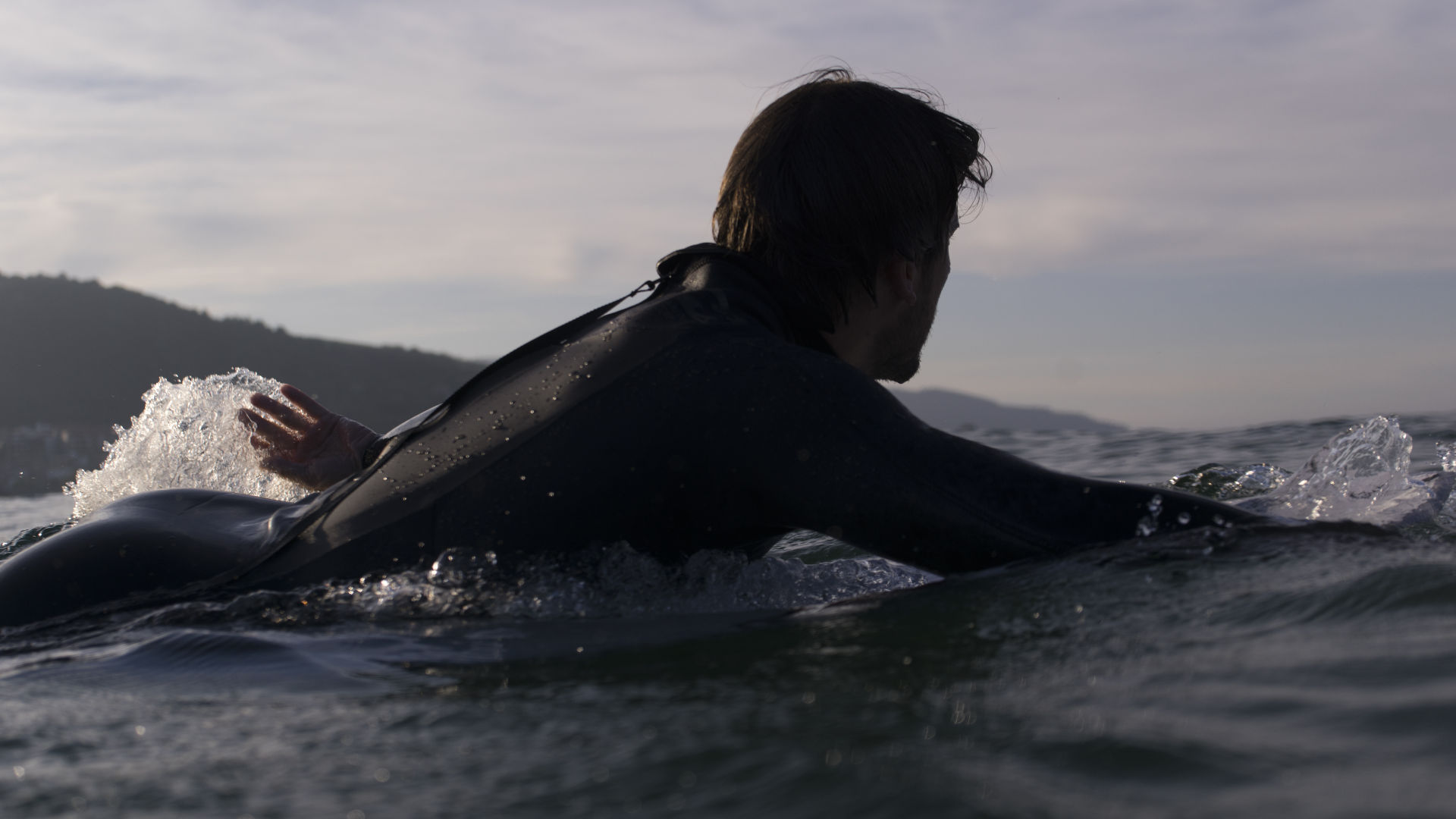 Surfer paddling out with a back zip wetsuit