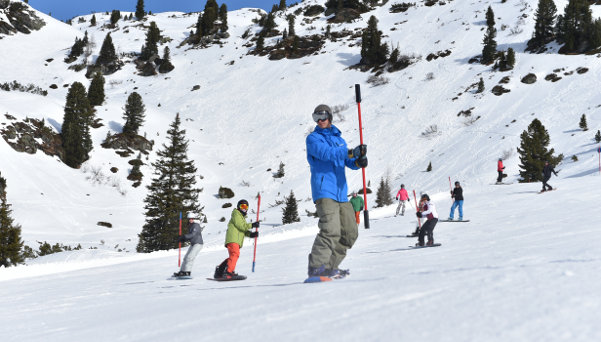 Snowboard teacher is leading the group doing exercises with a stick