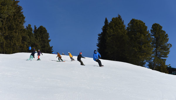 Group of snowboarders following the teacher