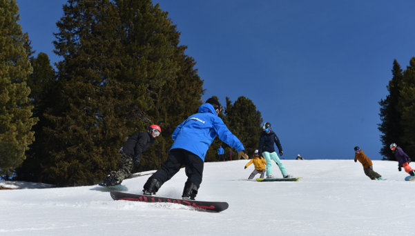 Snowboarding pupils following each other on the slope