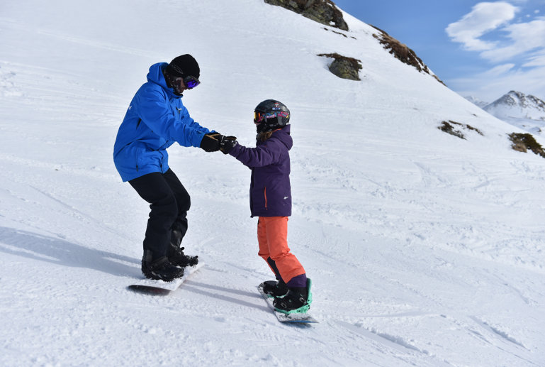 Snowboard teacher helping the pupil with first sliding exercise