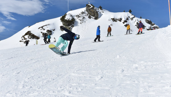 Pupil doinig nose wheely on a snowboard