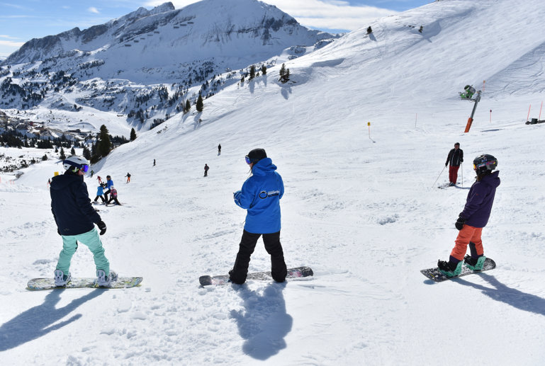 Snowboard instructor is talking to the pupils