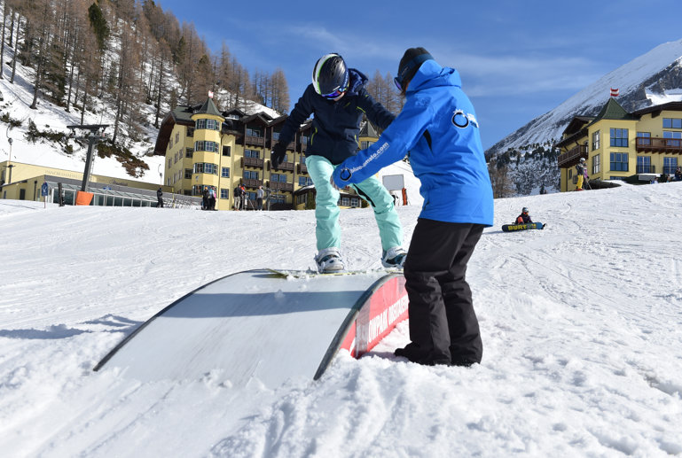 Snowboard Instructor is helping the student sliding over a box