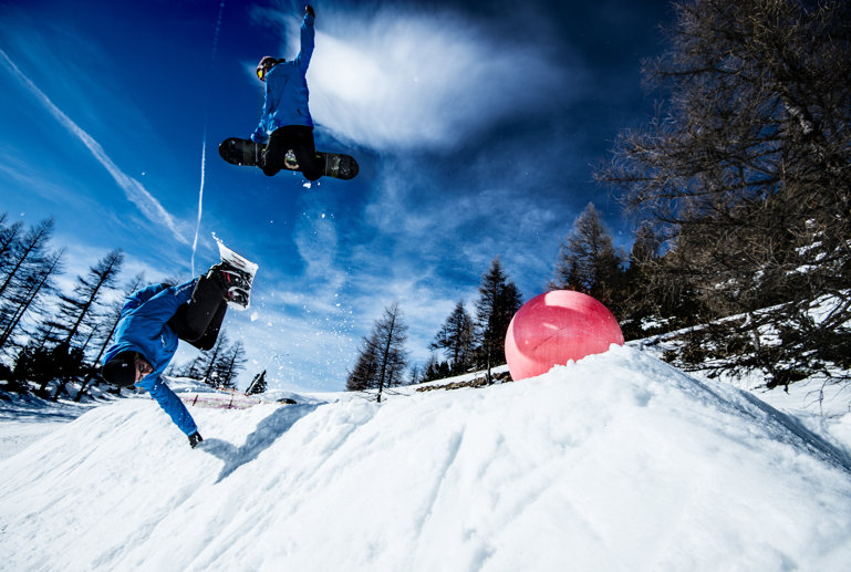 Two Blue Tomato Snowboard instructors jumping over a corner