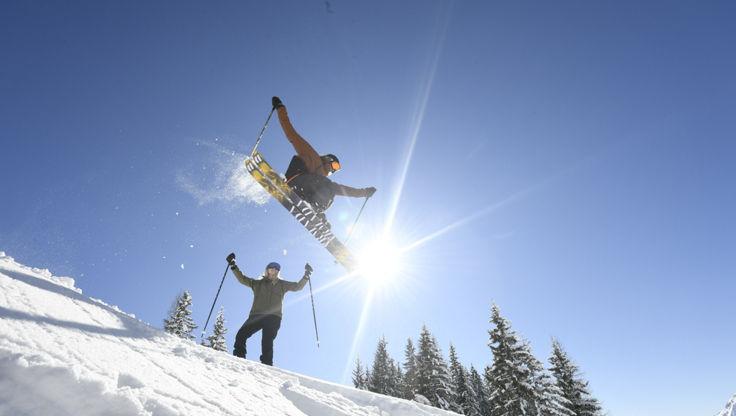 Ein Freeskier springt vor einer jubelnden Skifahrerin