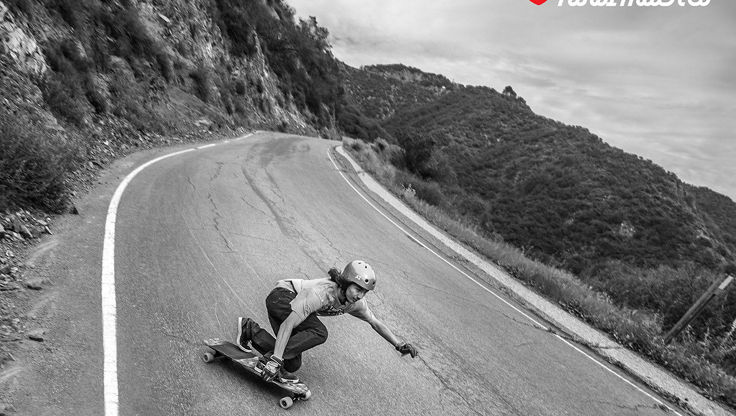 Longboarder kneeing on his Board with skate protection