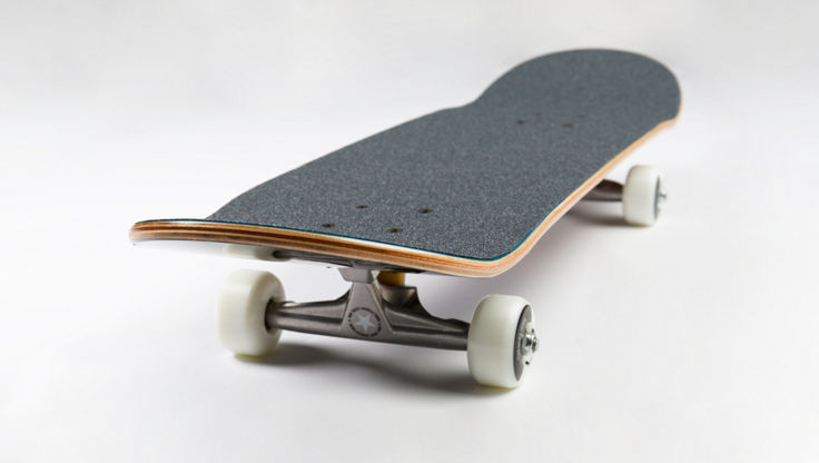 Complete skateboard in profile showing the kicktails