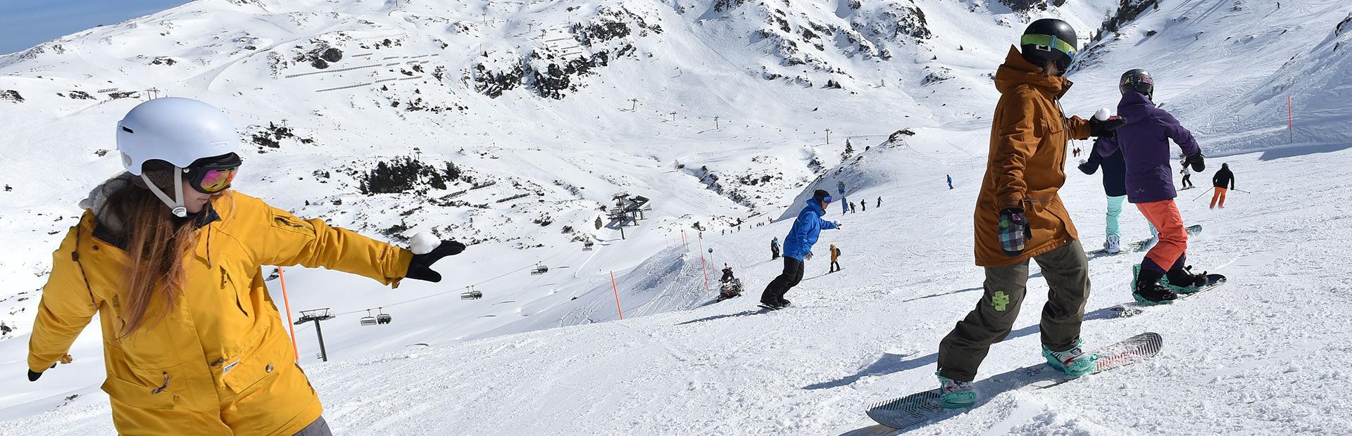 Snowboardschüler fahren hintereinander auf der Piste