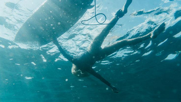 Mädchen im Meer neben ihrem Surfboard mit der Leash an ihrem Knöchel befestigt