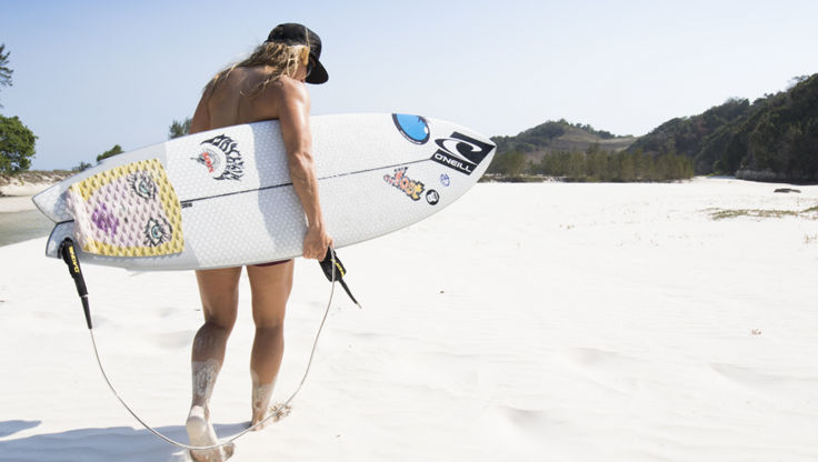 Girl on the beach carrying her surfboard which has traction pads on it