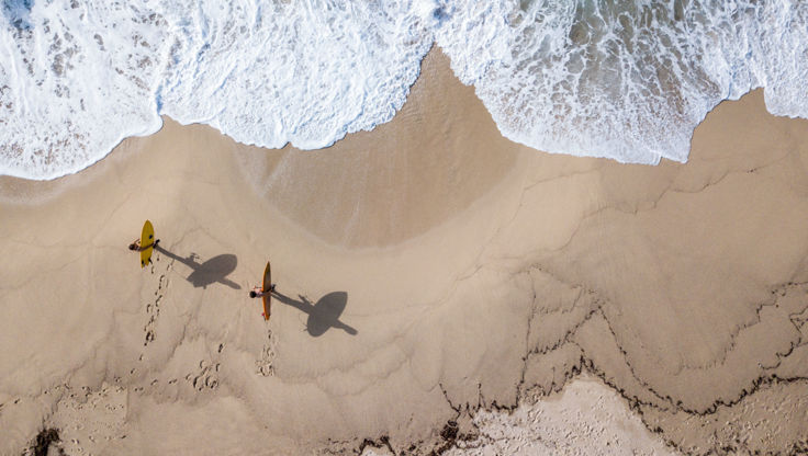 Zwei Anfänger mit Surfbrettern in der Hand am Strand