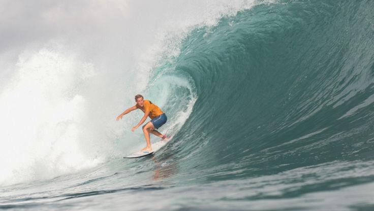 Blue Tomato Team Rider bei einem backside Surfmanöver auf einer grünen, brechenden Welle