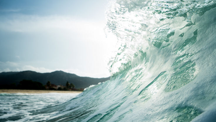 Un'onda verde che si gonfia e sta per raggiungere il punto di rottura